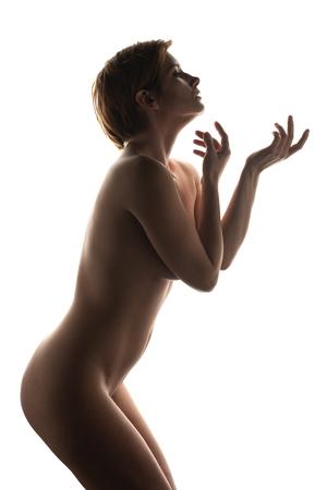 Mature English redhead nude in deep shadow on white Standard-Bild - 120649876