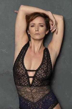 Rousse anglaise mature dans un body noir et bleu révélateur Banque d'images