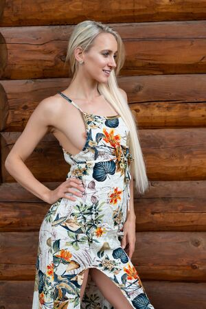 Beautiful slender young blonde in a long print dress Stock Photo