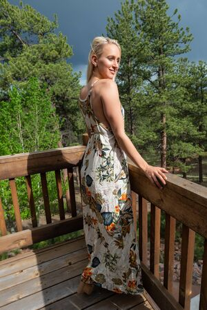 Beautiful slender young blonde on a rustic wooden deck
