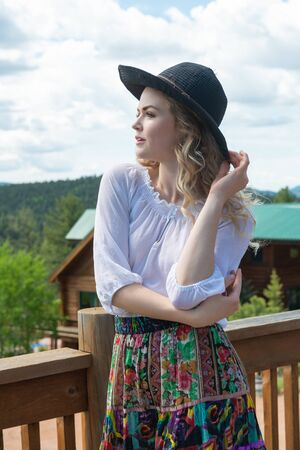Beautiful young wavy haired blonde in a white blouse and colorful print skirt