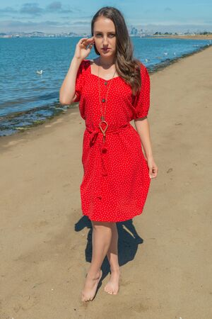 Petite young brunette in a red dress standing on a beach