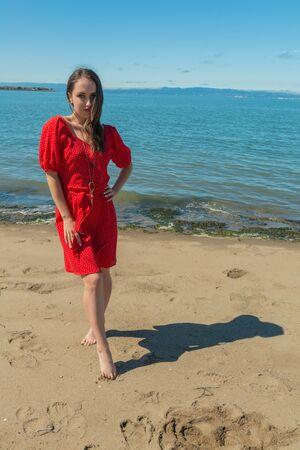 Petite jeune brune vêtue d'une robe rouge debout sur une plage