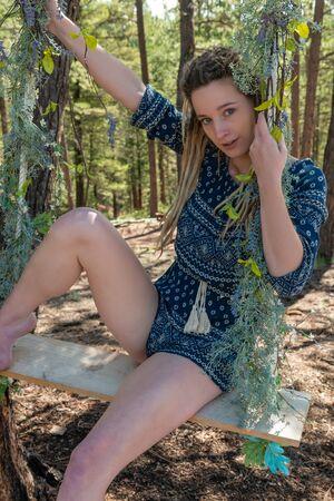 Hübsche zierliche junge Blondine in einer Baumschaukel