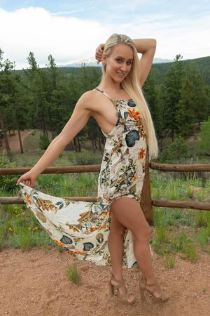 Beautiful slender young blonde in an alpine forest setting
