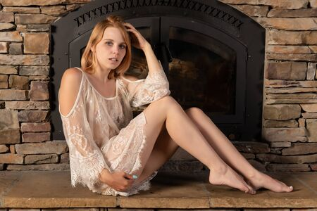 Pretty petite young blonde in a white lace negligee