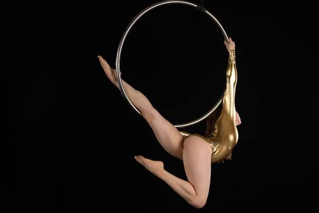 Petite athletic brunette acrobat suspended from an aerial ring