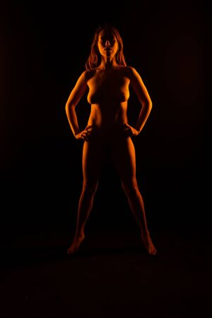 Petite young brunette standing nude in orange light