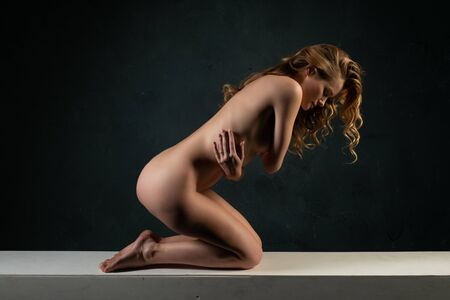 Beautiful tall blonde woman lying nude on a white beam