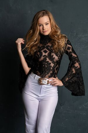 Beautiful tall blonde woman in a black lace blouse and white slacks