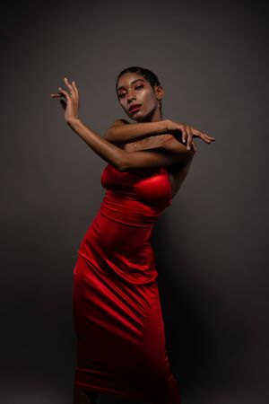Slender young African American woman in a tight red dress 免版税图像 - 142548336