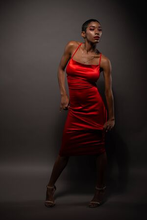 Slender young African American woman in a tight red dress Standard-Bild