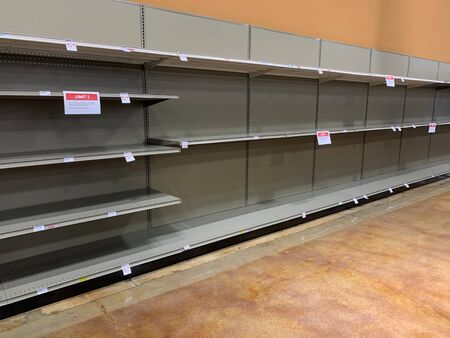 Supermarket shelves displaying an absence of goods for sale 免版税图像