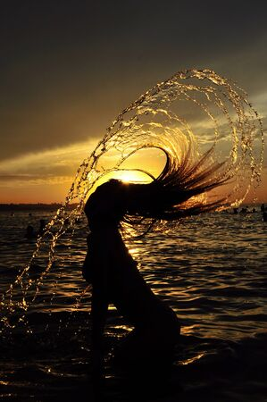 Women leaving the water at sunset with the hair throwing water photo