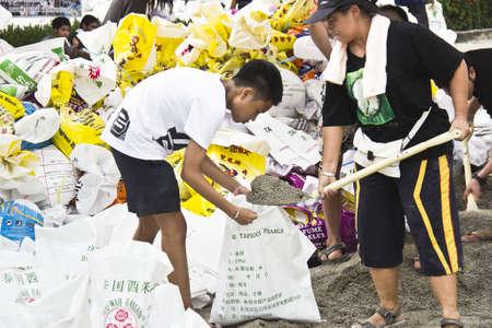 grinta: Volontari tailandesi riempire la grinta in sacchi di sabbia per bloccare l'acqua da inondazioni in Nakornnayok provincia, in Thailandia 15 ottobre 2011 Editoriali