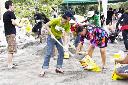 Thai volunteers fill the grit into sandbags to block the water from flood disaster in Nakornnayok province, Thailand in 15 October 2011 Editorial