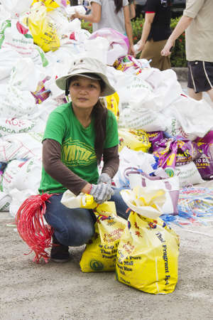 Thai volunteers tied sandbags to block the water from flood disaster in Nakornnayok province, Thailand in 15 October 2011