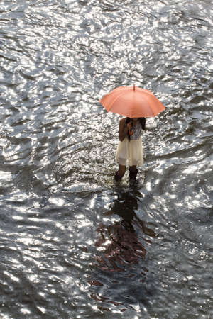 Bangkok Thailand 8 November 2011: A working women hold an umbrella to protect the heat from the sun, ware a long rubber boots, walking across the road to buy goods from convenience stores. Stock Photo