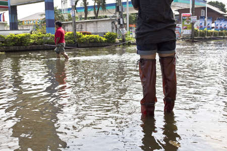 Bangkok Thailand 9 November 2011: In flooding situation in Thailand, Thai people wear a long boots to protect them self from disease from dirty water, but some are not.