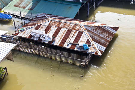 distric: Bangkok Thailand October 2011: Flood in to Pak kret market, Nonthaburi province, the water from Chao praya river flow into house almost cover the roof. Editorial