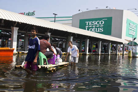Bangkok Thailand 12 November 2011: Flooding situation in Thailand, Many families  tried to hoarding goods by shopping from Lotus department store at Sapan Mai, Bangken distric. Because the water very high, many customer use the boat or bamboo raft instead