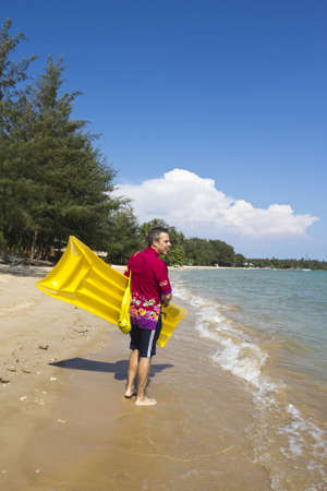 one senior man only: The  European man walking and carrying a yellow rubber mattress at the beach at Koh Mak island, Trat, Thailand