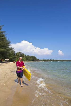 The  European man walking and carrying a yellow rubber mattress at the beach at Koh Mak island, Trat, Thailand
