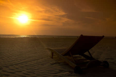 deck-chair on the beach with sunset  photo