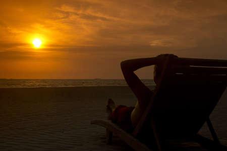 A European tourist on the deck-chair watching sunset