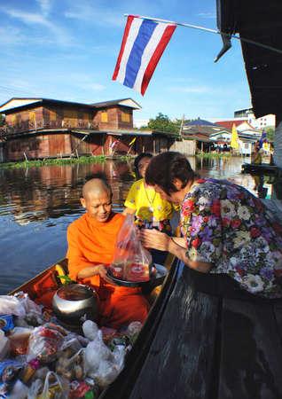 recieve: Buddhist monks recieve food from thai woman
