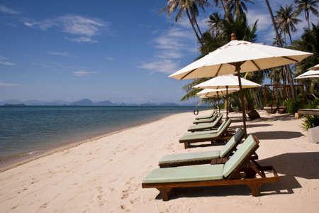 The beach deck-chair and umbrellas