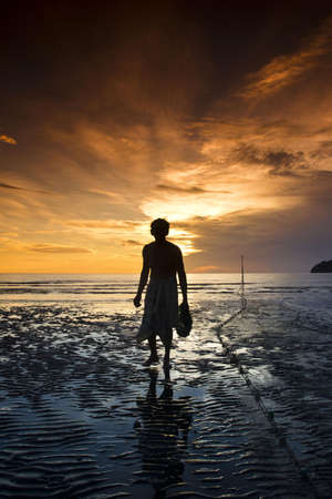 The old fisherman walking on the beach in the morning at Pranburi Prachuab kirikarn  photo