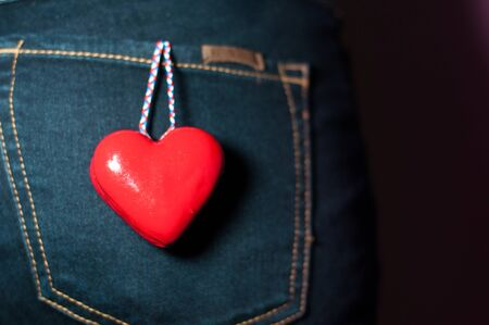 Woman back with red heart in pocket love concept