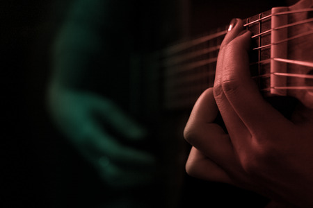 Woman beat guitar: Woman hands playing classical guitar in the dark Kho ảnh