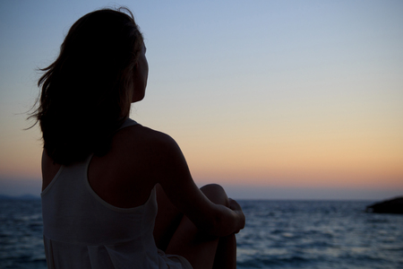 melancholia: Woman silhouette watching sunset, sitting alone by the sea Stock Photo