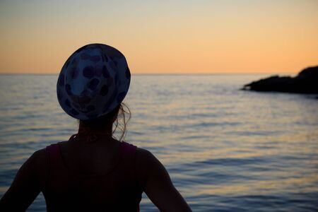melancholia: Young woman watching the sea summer sunset Stock Photo