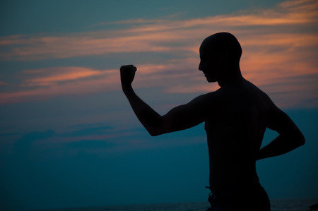 Sunset silhouette of a man practicing martial arts Stock Photo
