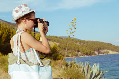 holiday maker: Young woman photographer, tourist using digital camera taking photo by the sea