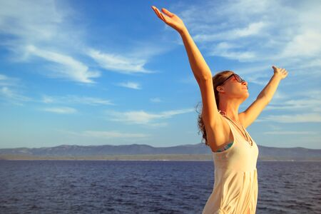woman hands up: Cheerful young woman with hands up, expressing joy, happiness, freedom standing by the sea