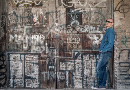 graffiti background: Man in jeans on graffiti background