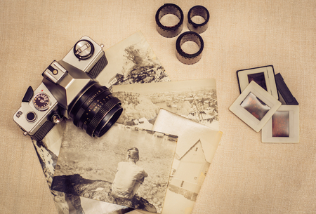 old photographs: Retro photo camera with old photographs, film rolls and slides. Vintage stylized.