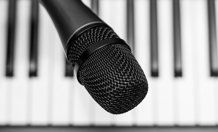 composing: Close up microphone on piano keyboard in music studio. Music concept. Stock Photo