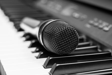 Close up microphone on piano keyboard in music studio. Music concept. Stock Photo