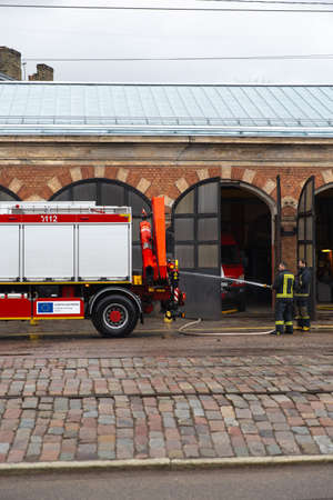 RIGA, LATVIA - MARCH 16, 2019: Fire truck is being cleaned - Driver washes firefighter truck at a depo - Van in a garage
