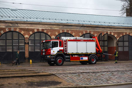 RIGA, LATVIA - MARCH 16, 2019: Fire truck is being cleaned - Driver washes firefighter truck at a depo - Old man passing by Editöryel