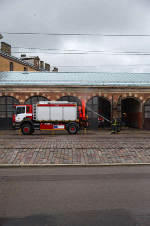 RIGA, LATVIA - MARCH 16, 2019: Driver washes firefighter truck at a depo from behind - Fire truck is being cleaned