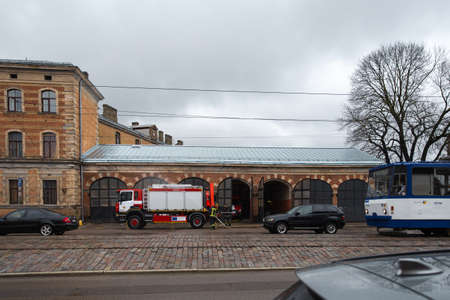 RIGA, LATVIA - MARCH 16, 2019: Fire truck is being cleaned - Driver washes firefighter truck at a depo
