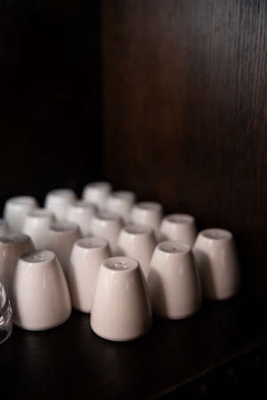 Many white salt shakers in a bar restaurant and pub