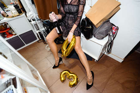 A woman resting on floor and drinking champagne glass at her birthday party - Long hot legs