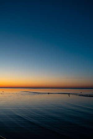 Lebhafter erstaunlicher Sonnenuntergang im Baltikum - Dämmerung im Meer mit Horizont, der von der Sonne beleuchtet wird